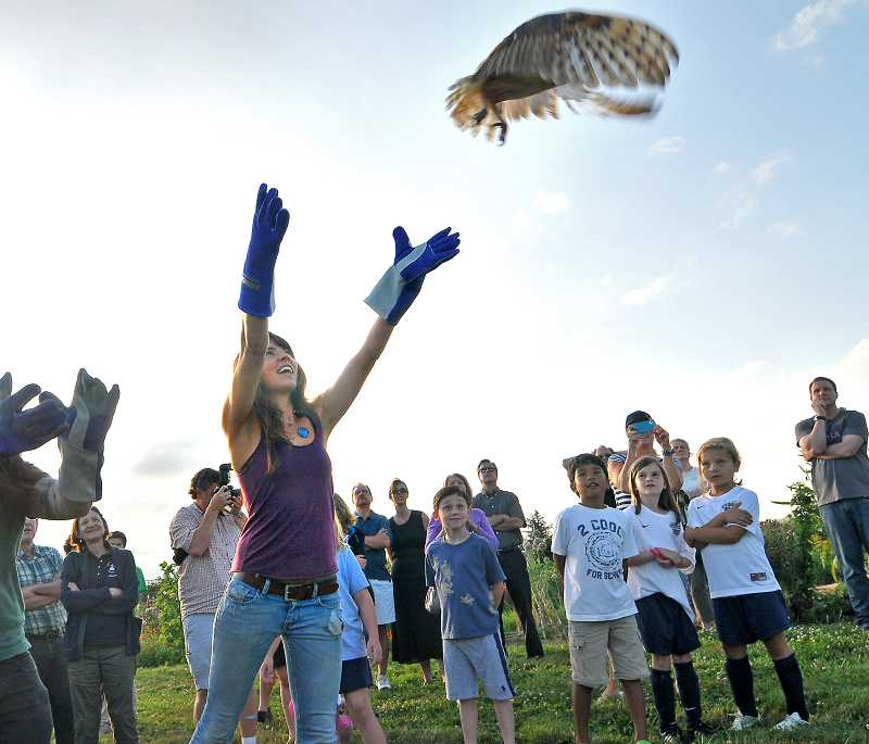 by: VERN UYETAKE - Stephanie Bartlett, a 2011 graduate of West Linn High School, has a big smile as she releases a barn owl at Lake Oswego's Luscher Farm Friday.