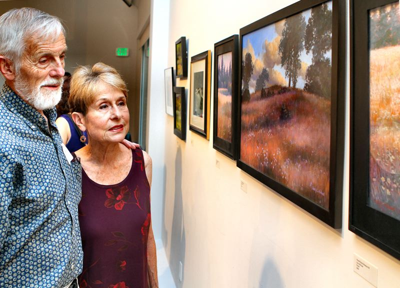 by: DAVID F. ASHTON - Artist Gary L. Michael shows to his wife, Oregon Rep. Carolyn Tomei, his entries in the art show.