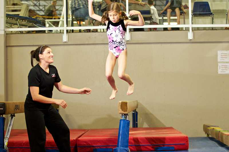 by: JAIME VALDEZ - Sydney Flynn jumps off a balance beam under the watchful eyes of Oregon Gymnastics Academy coach Katie Candeaux.