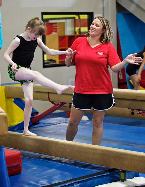 by: JAIME VALDEZ - Oregon Gymnastics Academy coach Bobbie Duncan assists student Allyson Hooge during practice last week. Oregon Business magazine named OGA the No. 3 Top Large Nonprofit to Work For in Oregon.