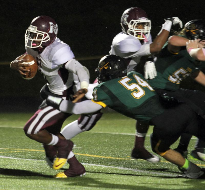 by: JONATHAN HOUSE - Milwaukie quarterback Richard Ramsey slips an attempted tackle by Putnam senior lineman Moein Rezaei (54) in last Fridays 46-26 win at Putnam, while teammate Kendrick Bourne throws a block. Ramsey had a big game, as he led the Mustangs to victory, rushing for 245 yards and two touchdowns, and passing for 166 yards and three touchdowns.