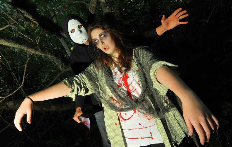 by: VERN UYETAKE - Mike Perkins nabbed Tori Smith as part of the scare tactics at a previous Haunted Trail in West Linn's Mary S. Young Park.