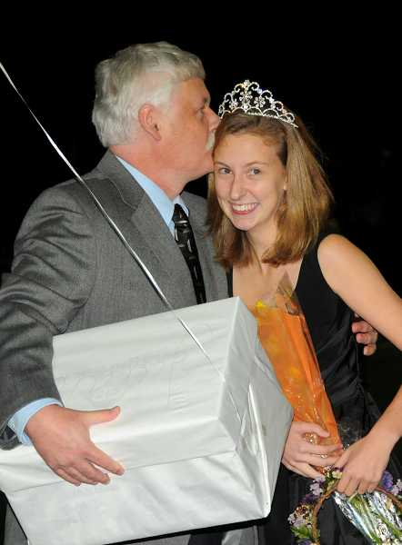John Sutton gives his daughter, Sarah, a kiss after she is crowned homecoming queen.