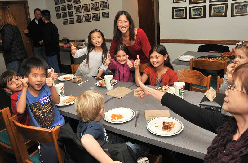 by: VERN UYETAKE - Jenni Tan get a thumbs-up from family and friends at Round Table Pizza on Tuesday evening.