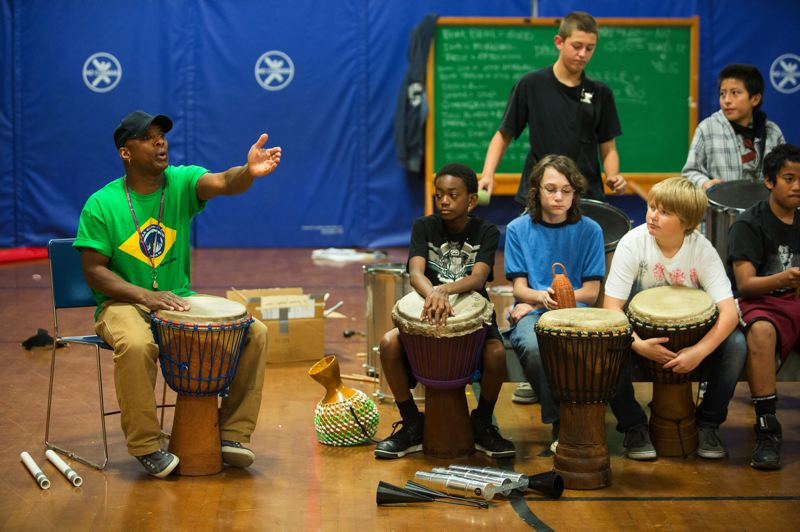 by: TRIBUNE PHOTO: CHRISTOPHER ONSTOTT - Chuk Barber teaches African-Brazilian drumming and dance to middle-schoolers at Faubion K-8 School. Boys and girls of all races are enrolled in the class. That's not the case at Barber's other school, Harvey Scott K-8.