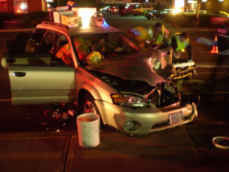by: OREGON STATE POLICE - Clackamas County Fire District No. 1 crews assist Oregon State Police at the crash scene Saturday nigh in Oak Grove.