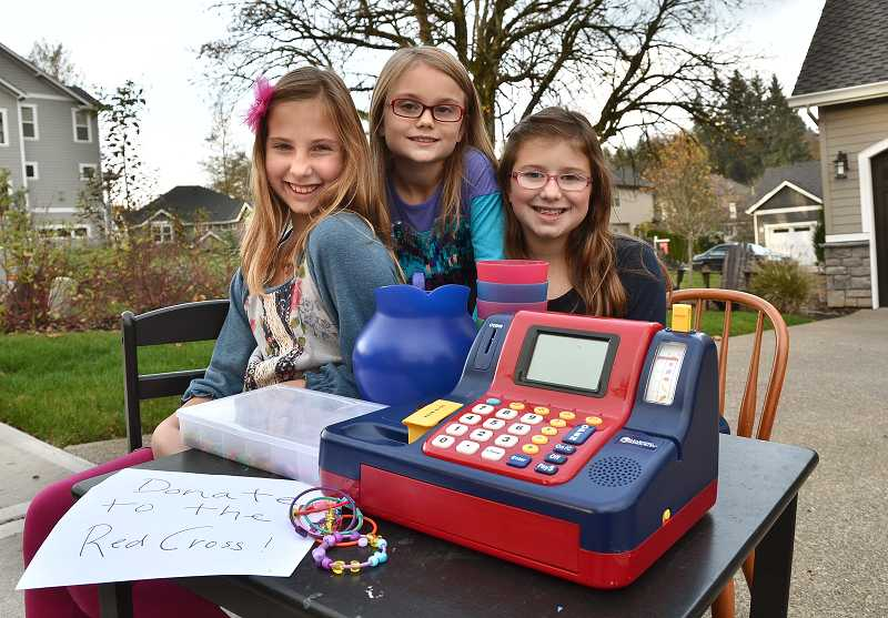 by: VERN UYETAKE - West Linn girls, Emery Johnston, 10, Halle Beck, 8, and Bridget Johnston, 8, sold lemonade and bracelets for the Red Cross.