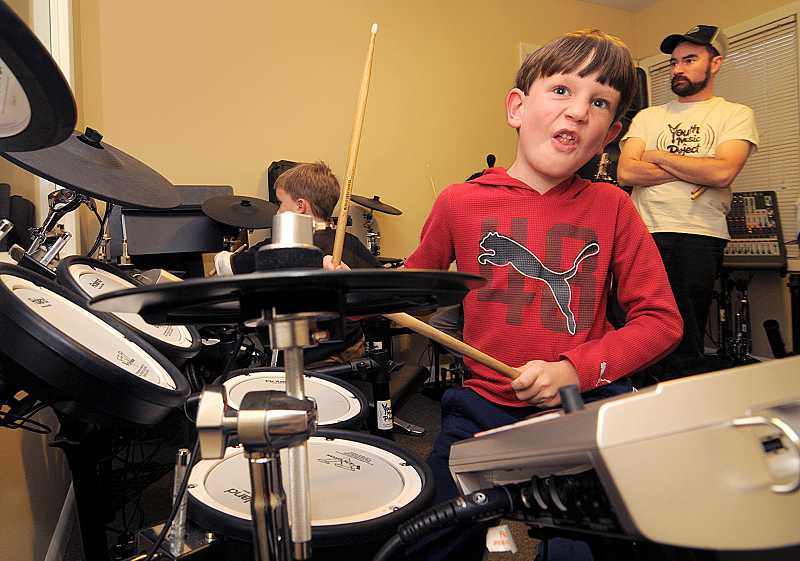 by: VERN UYETAKE - Bucky Brand practices his drumming skills on Nov. 13 at Youth Music Project.