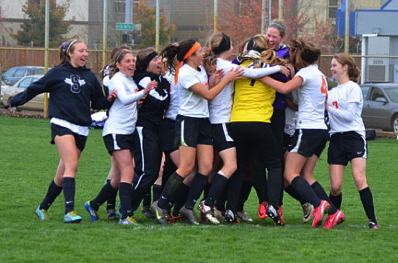 by: JOHN BREWINGTON - The Scappoose Lady Indians enjoy a well-deserved group hug (above) and celebration after edging La Salle Saturday in an overtime game. The Tribe girls led much of the match, but La Salle evened the score late in regulation. Neither team could score in overtime and the game went to penalty kicks.