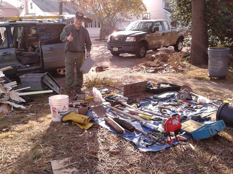 by: SUBMITTED - Tom Nielsen of Lake Oswego gives the thumbs-up sign after organizing a supply of tools. A native of New Jersey, Nielsen was determined to help victims of Sandy.