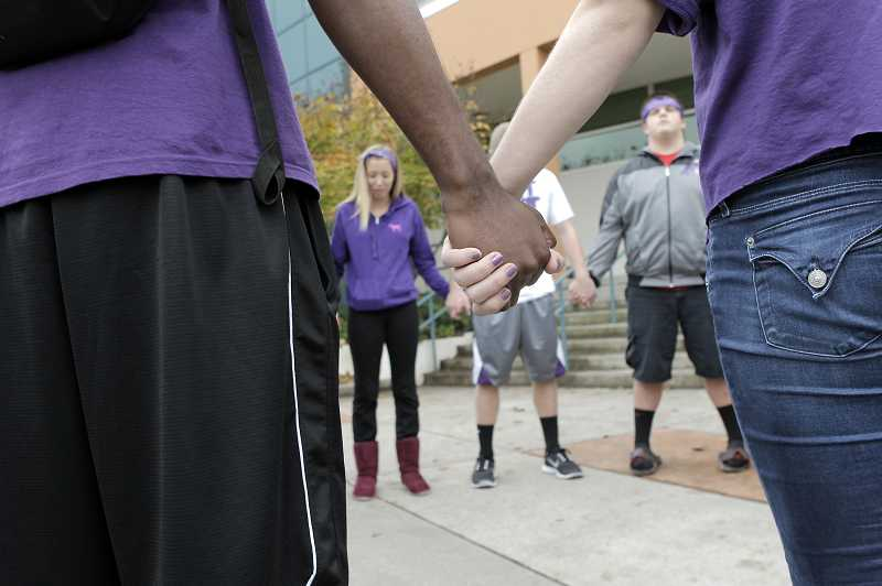 by: JAIME VALDEZ - A group of Beaverton High School students form a prayer circle on Tuesday afternoon outside the school in remembrance of Maddie Lauer, a freshman who died on Sunday. Many dressed in purple shirts and ribbons to represent Maddie's favorite color.