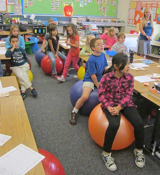 by: BARBARA SHERMAN - SOFT SEATS - Participating in classroom activities is more fun for Hopkins Elementary second-grade students like Payzlee Sarano-Ramos and Corbin Patterson (on the right) when they sit on exercise balls, and teacher Sari Hedges (rear) sees the benefits of using them.