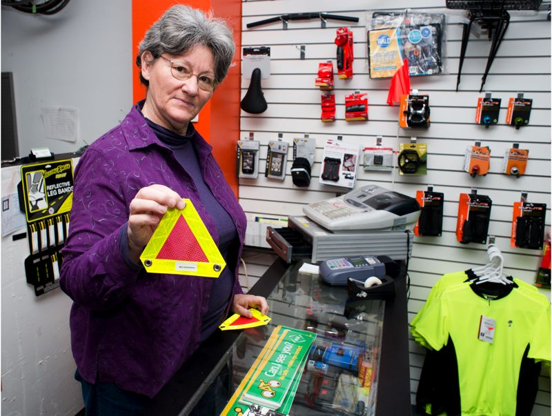 by: TRIBUNE PHOTO: CHASE ALLGOOD - Nancy Nelson shows off one of her pedigreen.com reflective triangles.