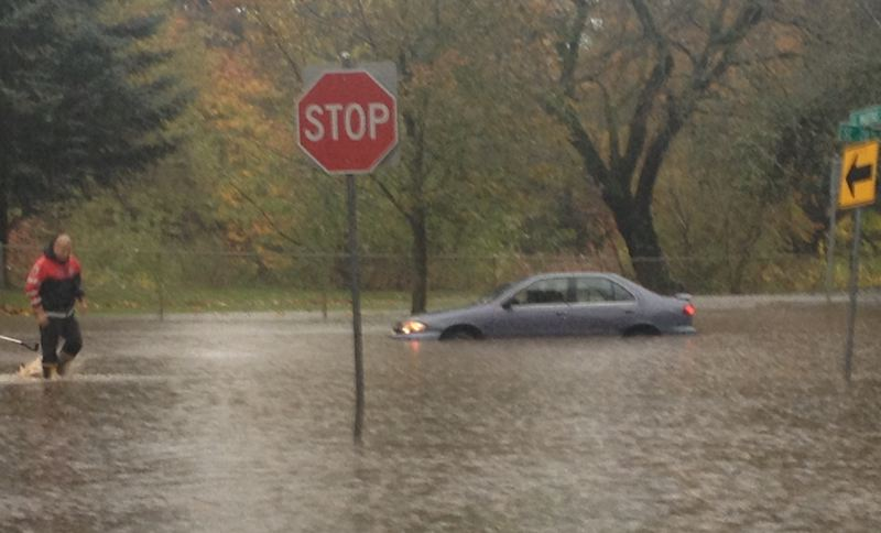 by: COURTESY OF WILLA GRUND - A car was stuck Monday afternoon in high water at Southeast 28th Avenue near the Eastmoreland Golf Course. Portland firefighters helped the stranded occupants to safety.