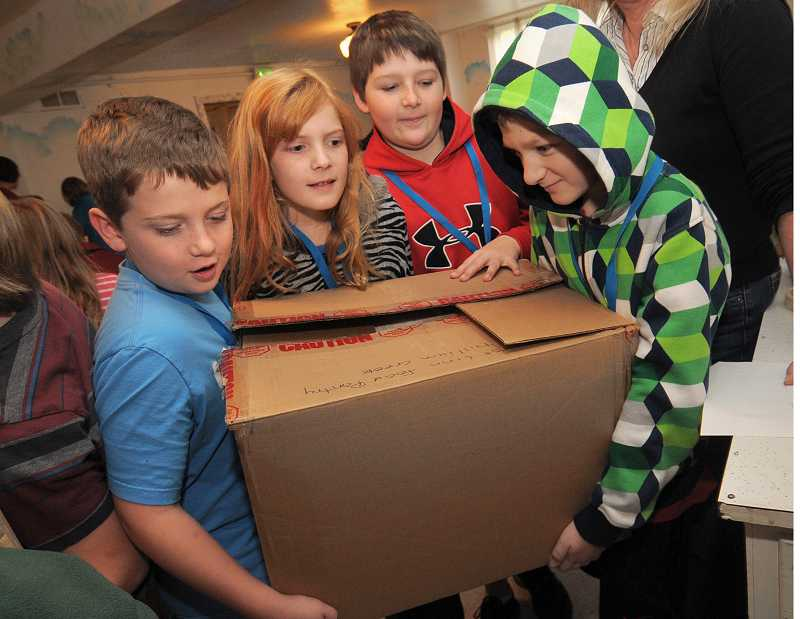 by: VERN UYETAKE - From left, Thomas McNamara, Allison Griffiths, Jayder Bornia and Evan Schleef get ready weigh a box of West Linn Food Pantry donations from Trillium Creek Primary School.