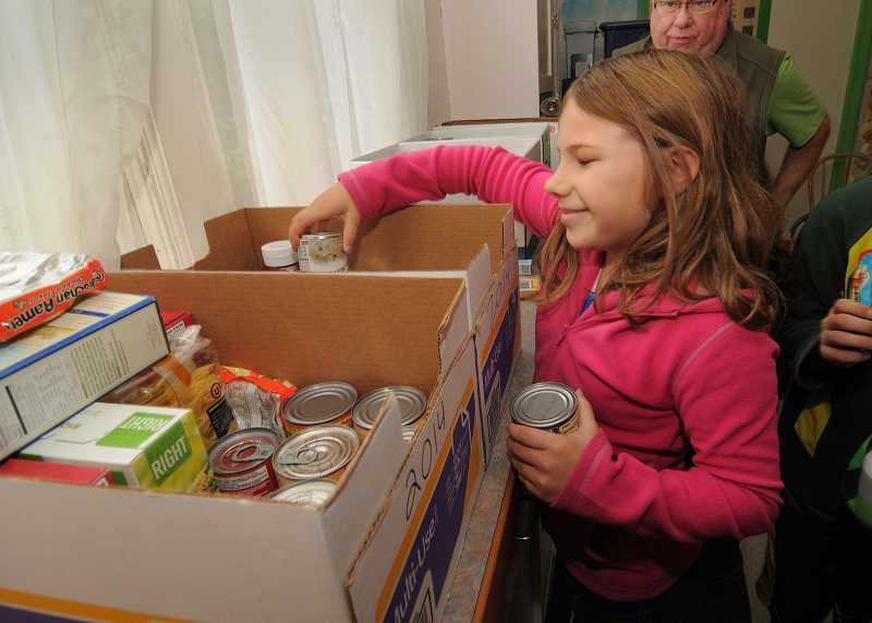 by: VERN UYETAKE - Jadyn Dewey helps sort food donations. Trillium Creek Primary donated 968 pounds of food.
