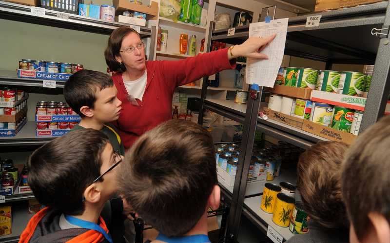 by: VERN UYETAKE - Jennifer Looney, co-director of the West Linn Food Pantry,  give students a tour of the facilities.