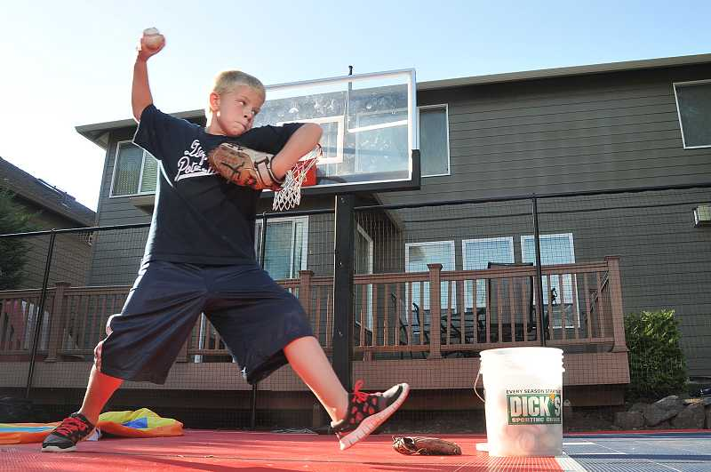 by: VERN UYETAKE - Zach Holmes, 10, practices his pitch at the sport court installed at his family home.