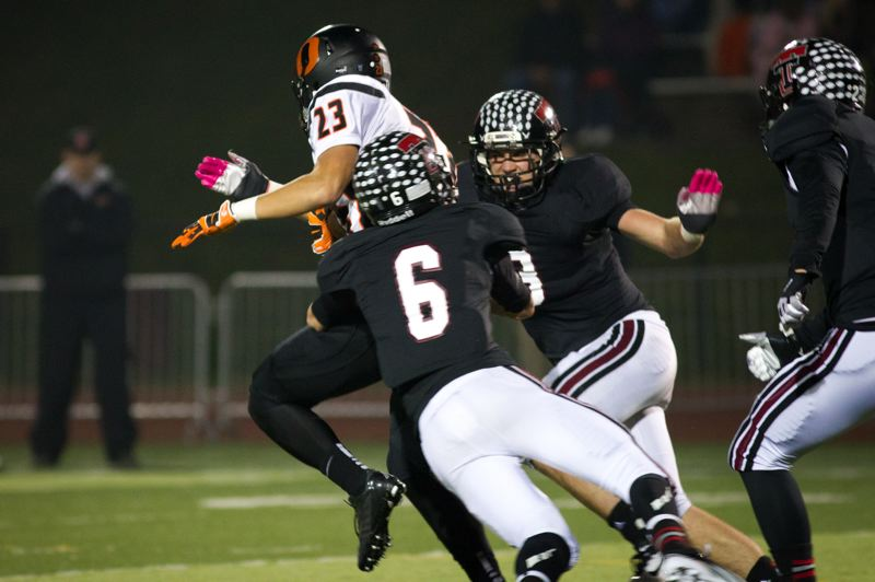 by: JAIME VALDEZ - TUALATIN TACKLE -- Tualatin  defenders Derek Senger (6) and Andrew Schlottmann (3) tackle wide receiver Tatlor Brotton in the 6A quarterfinal playoff game at Tualatn High School. The Olympians scored a 10-0 win in the second-round postseason contest.