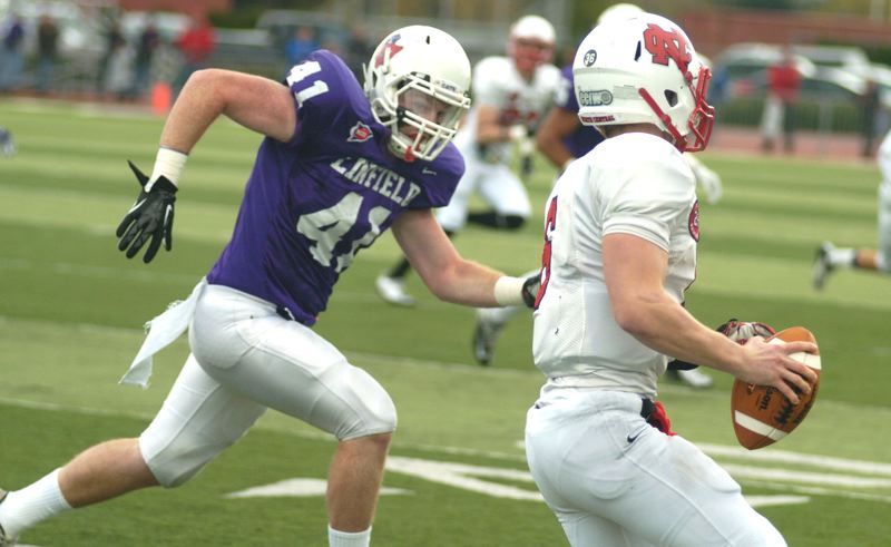by: PAMPLIN MEDIA GROUP: DAVID BALL - Linfield linebacker Brynnan Hyland chases North Central QB Spencer Stanek during the first quarter of the Wildcats 30-14 playoff win Saturday.