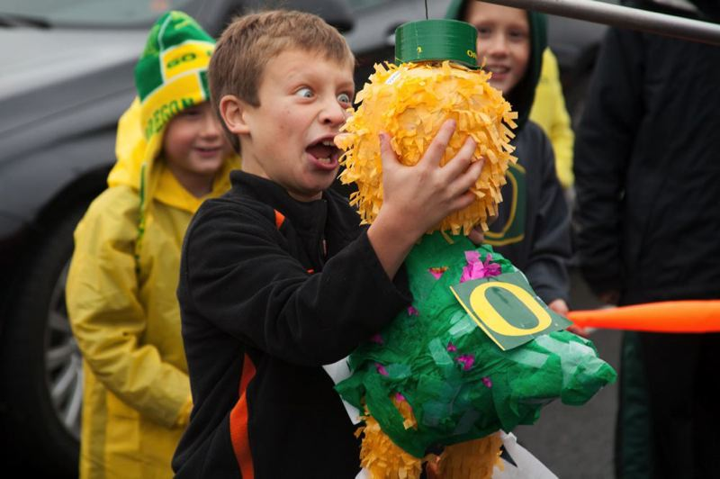 by: TRIBUNE PHOTO: MEG WILLIAMS - A young fan has fun with a Duck pinata before Saturday's noon kickoff.