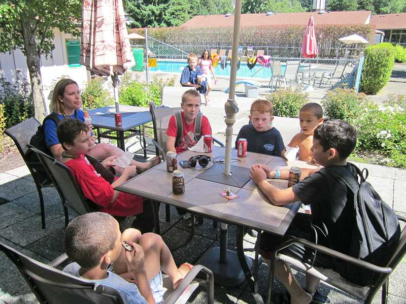 by: BARBARA SHERMAN - THE GOOD LIFE - Elizabeth Schmidt, the Good Neighbor Center's student/parent advocate, supervises the kids while they enjoy their snacks after swimming in the KCCA pool.