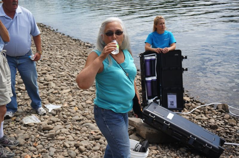 by: PHOTO COURTESY: OLWD - Newly elected Oak Lodge Water District Commissioner Nancy Gibson samples a bottle of water pulled last week from the Willamette River near the boat ramp in Meldrum Bar Park and treated using a portable emergency water filtering system demonstrated by Tamra Helm.