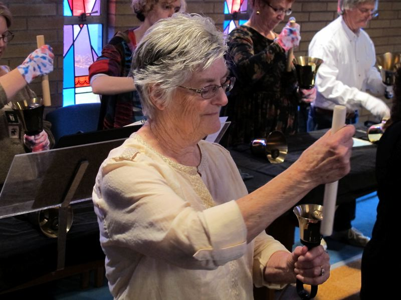 by: HILLSBORO TRIBUNE PHOTO: KATHY FULLER - Carolyn Snyder uses a wooden dowel to make a handbell sing. Snyder has directed the handbell choir at First Congregational United Church of Christ in Hillsboro for 35 years.