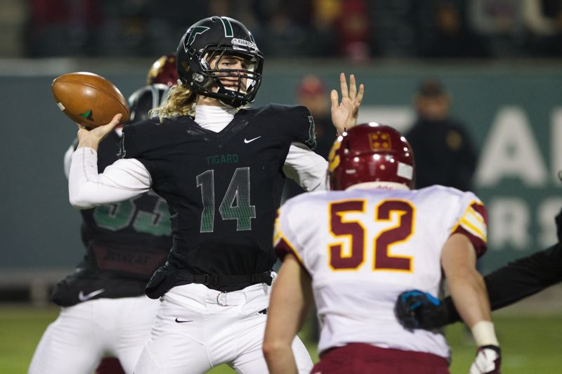 by: JAIME VALDEZ - PASSING FANCY -- Tigard senior quarterback Jett Even (left) looks to throw a pass over Central Catholic senior Donovan Manning. Even passed for 306 yards in Saturday's state playoff semifinal contest.