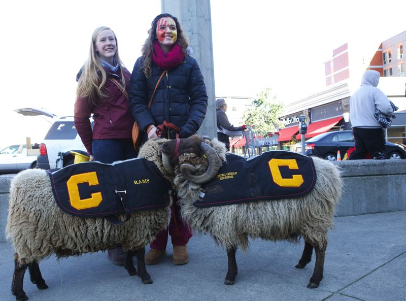 Central Catholic High seniors Katie Kehoe and Jordan Badden pose with Lancelot and Romeo, rams owned by Rhonda Elledge, before the state championship football game Saturday at Jeld-Wen Field.