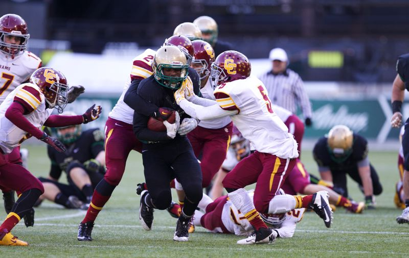 by: TRIBUNE PHOTO: JAIME VALDEZ - Chase Morrison, Jesuit running back, slices through the Central Catholic defense in Saturday's state championship game.