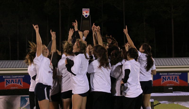 by: COURTESY OF CONCORDIA UNIVERSITY - Concordia University players lift the championship trophy after claiming the NAIA women's soccer crown.