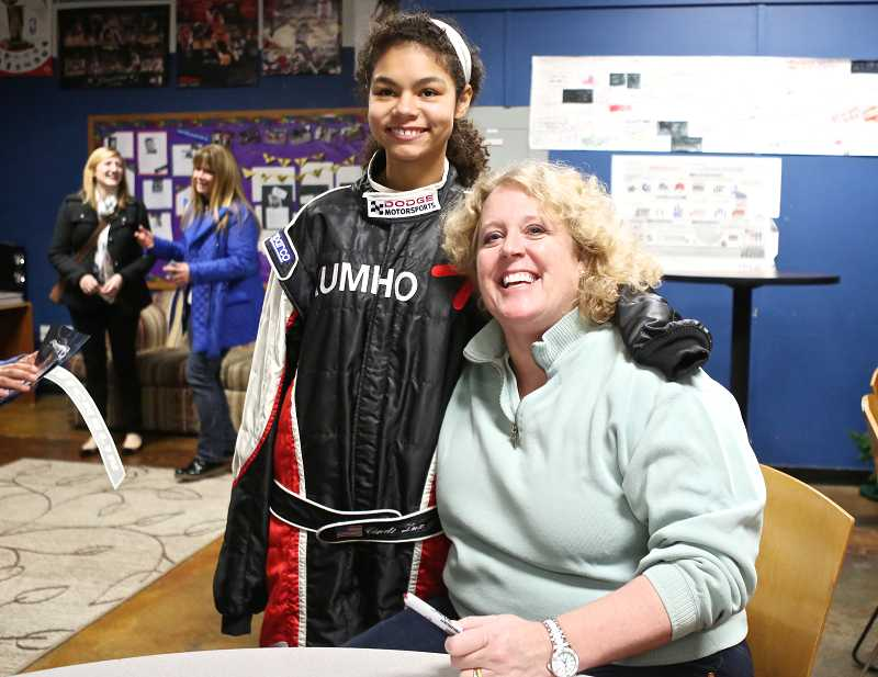 by: TIMES PHOTO: JAIME VALDEZ - Marea Hines, 12, poses for a picture with race-car driver Cindi Lux in Lux's racing suit.