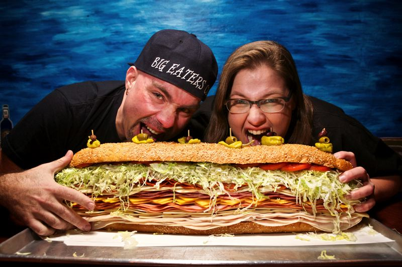 by: TRIBUNE PHOTO: JAIME VALDEZ - Stephanie Collingsworth and Ryan Rodacker, founders of the Portland Big Eaters Club, take the measure of the best that the Mad Greek Deli on East Burnside Street has to offer. The couple insists that when it comes to competition eating, fat gets in the way.