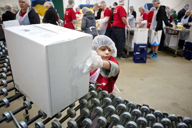 by: TIMES PHOTO: JAIME VALDEZ - Gideon Batie, 6, loads a box of packaged corn on a conveyer belt in the cooler of the Oregon Food Bank in Beaverton. Batie helped her cousin, Ivory Berry, volunteer in her company's effort at the food bank's Day of Service to honor the Rev. Martin Luther King Jr.