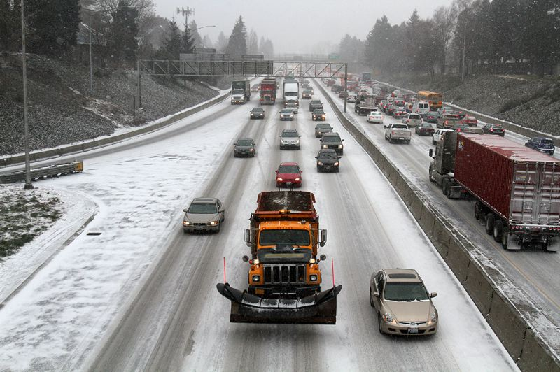 by: TRIBUNE PHOTO: JONATHAN HOUSE - A snow plow slow moves north in heavy traffic in North Portland Thursday afternoon. Rush hour started early as snow continued to fall.
