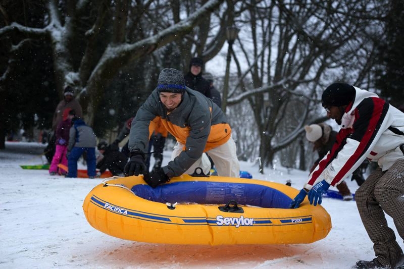 by: TRIBUNE PHOTO: JONATHAN HOUSE - Allen Chu, center, gets ready to ride an inflatable boat along with other winter revelers at Irving Park on Friday.
