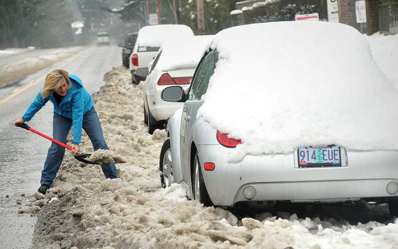 by: TIDINGS PHOTO: VERN UYETAKE - Lauren Huffman works hard to dig out her car parked along Highway 43 on Monday. Her car got stranded there two days earlier because of the snow and ice.