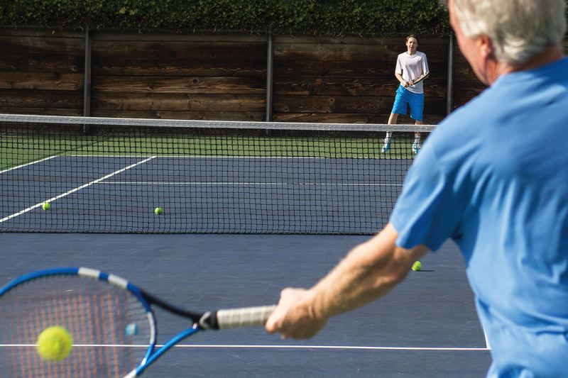 by: HILLSBORO TRIBUNE PHOTO: CHASE ALLGOOD - Dave Edwards (foreground) hits tennis balls to his son, Tommy Edwards, a Century sophomore and returning state tournament qualifier, during a recent practice session in Hillsboro.