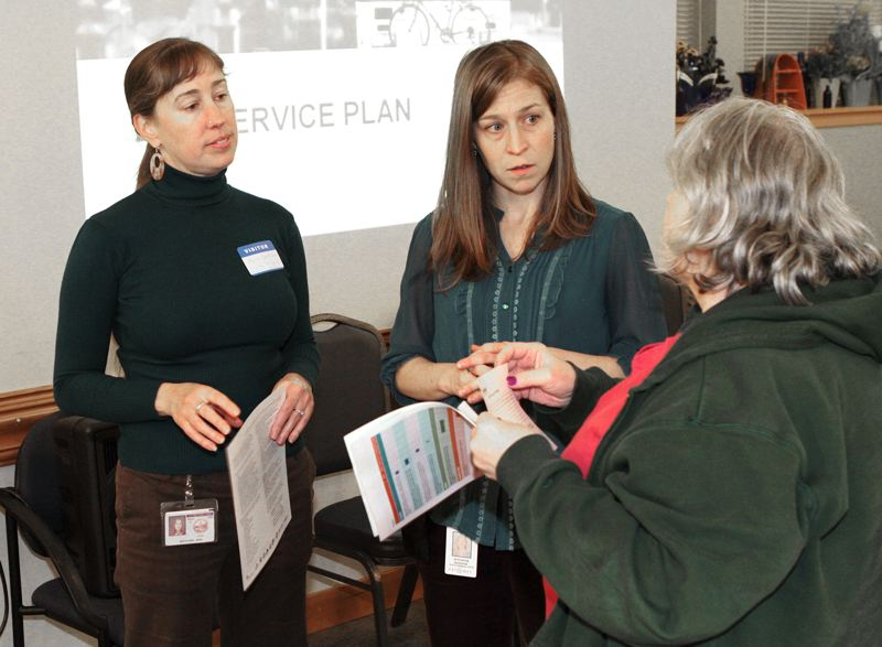by: DAVID F. ASHTON - Portland Bureau of Transportations April Bertelsen, and TriMet Portland-Milwaukie Light Rail Project Community Affairs Representative Jennifer Koozer, listen as a neighbor comments on proposed cuts to bus service in Inner Southeast.