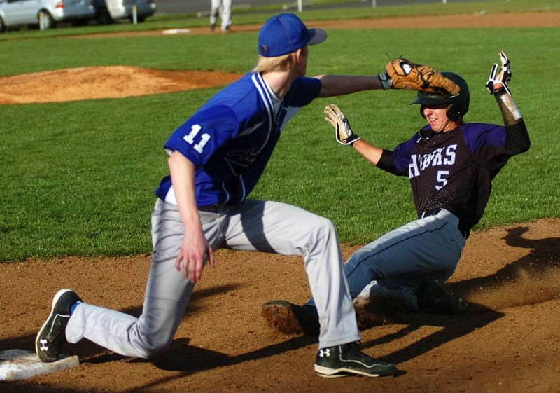 by: DAN BROOD - BACK IN TIME -- Horizon Christian senior Kyle Esquerra (right) slides back to first base ahead of the throw during the Hawks' league win over Amity.