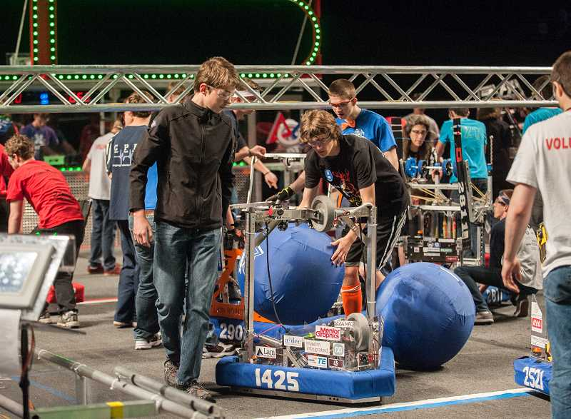 by: SPOKESMAN PHOTO: JOSH KULLA - Mechanical team lead Ryan Kelly, center, prepares his team's robot for competition.