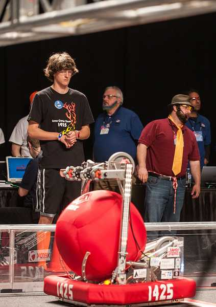 by: SPOKESMAN PHOTO: JOSH KULLA - Ryan Kelly, 1425's mechanical team lead, keeps a close eye on the Wilsonviille team's robot.