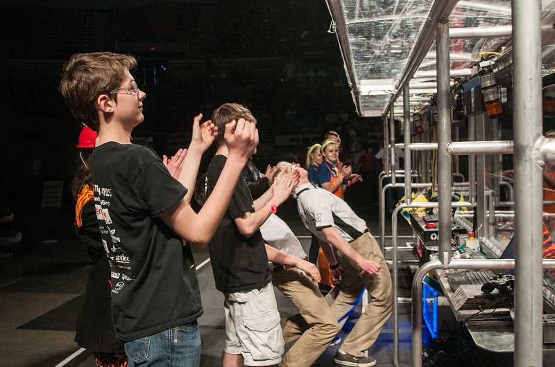 by: SPOKESMAN PHOTO: JOSH KULLA - Wilsonville High School robotics team members applaud their alliance teammates during a qualifying match at the Portland Regional at Memorial Coliseum last Friday.