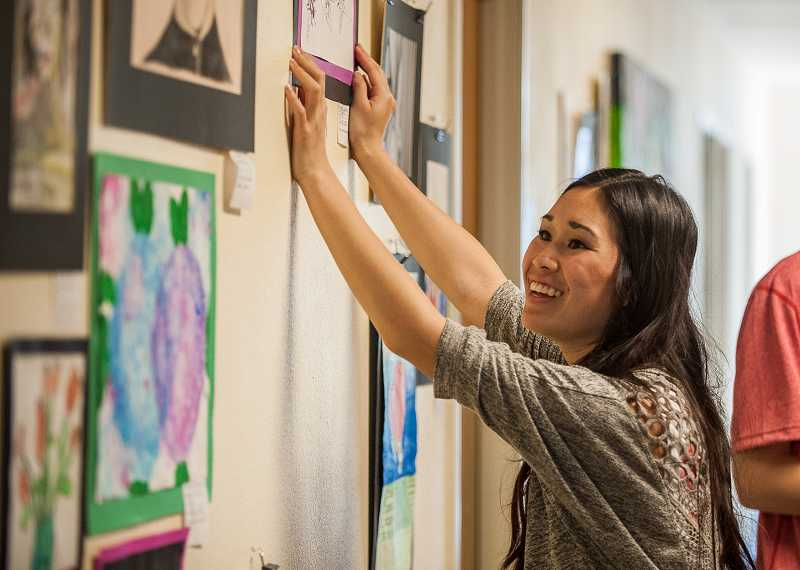 by: SPOKESMAN PHOTO: JOSH KULLA - West Linn High School senior Julia Casad helps install artwork last Friday at Art Tech High School in Wilsonville in preparation for the West Linn-Wilsonville School Districts district-wide art show.