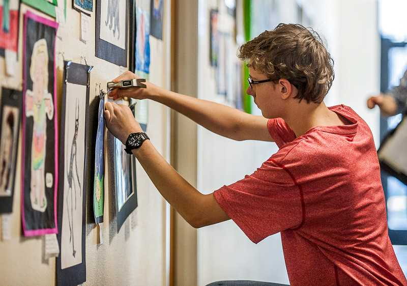 by: SPOKESMAN PHOTO: JOSH KULLA - Art Tech High School freshman Isaac Hascall straightens a painting as he helps prepare his school to host this year's district-wide art show April 19.