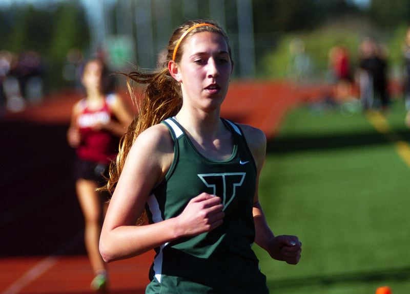 by: DAN BROOD - WINNER -- Tigard senior Megan Franz is first across the finish line in the 1,500-meter run.
