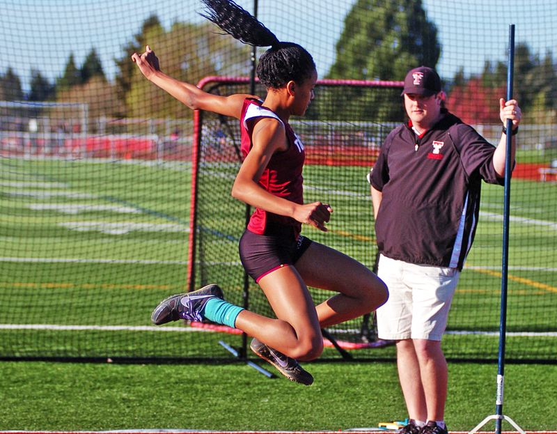 by: DAN BROOD - IN FLIGHT -- Tualatin sophomore Karina Moreland won both the long jump and triple jump events for the Timberwolf girls in their victory over Tigard.