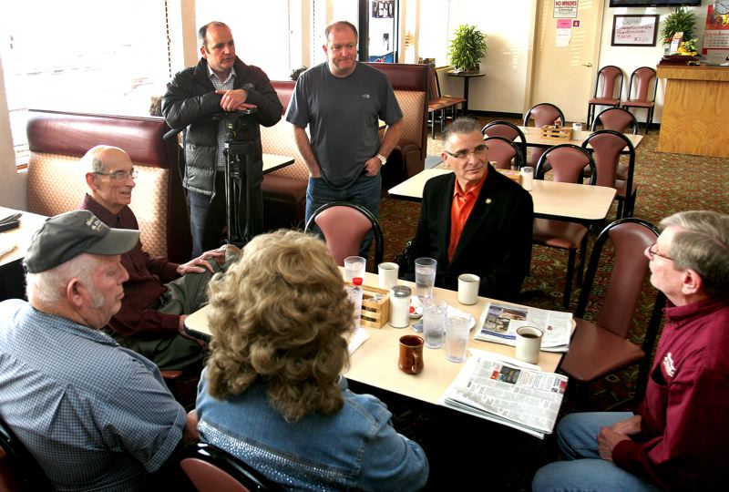 by: OUTLOOK PHOTO: JIM CLARK - BBC reporter Glenn Campbell and cameraman Andy Halley, standing left to right, met with locals at the Red Apple Restaurant in Boring. Clockwise from center are Rep. Bill Kennemer and his wife Cherie, Steve Bates, Glenda Boring, Bob Boring and Jim Hart.