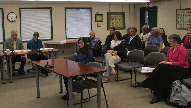 by: MARK MILLER - Jayden Alexander (foreground) sits as St. Helens School District Superintendent Mark Davalos (far left) reads a letter from St. Helens Middle School Principal Carol Dowsett (far right) announcing her receipt of the President's Volunteer Service Award on Wednesday, April 23. Alexander's parents sit behind her in the first row of audience seating.